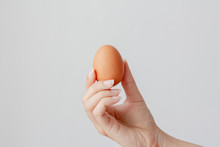 Hand Holding Egg On White Back...