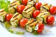 Leinwandbild Motiv Vegetarisch grillen: Bunte marinierte Feta-Spieße mit Zucchini, Kirschtomaten  und Kräutern - Grilled marinated feta skewers with Greek cheese, courgette, cherry tomatoes and herbs