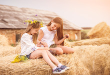 Cute Sisters In The Field With Cherry And Flowers