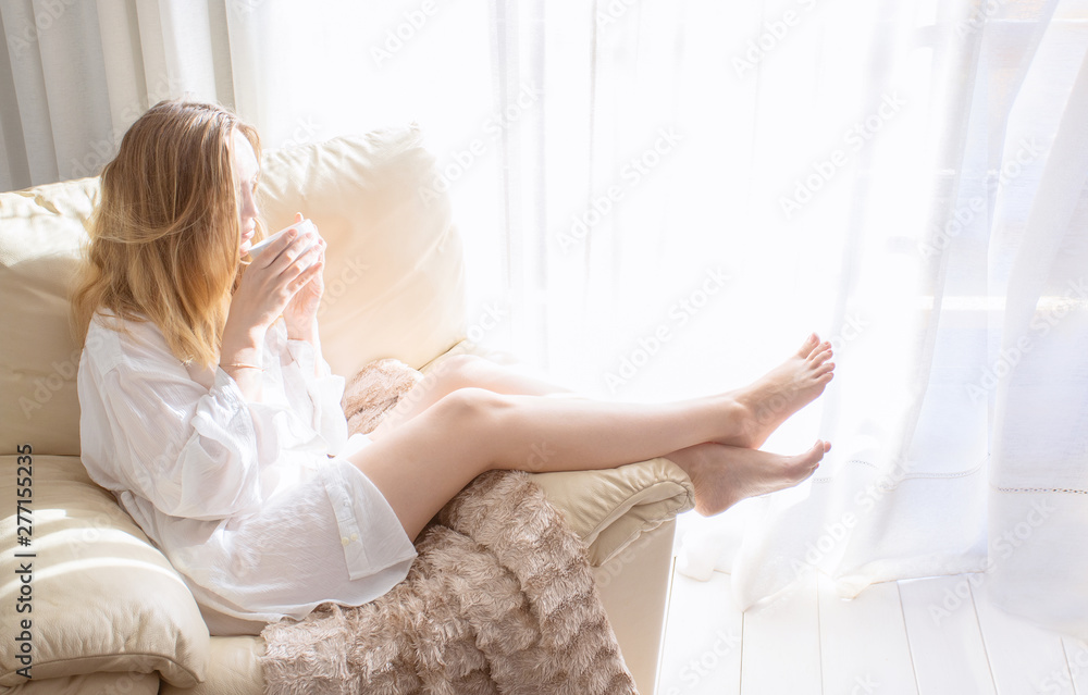 Fototapeta Woman sitting in white armchair and drinking coffee at the morning in bedroom. Relaxing and good morning concept.