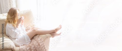 Spoed Foto op Canvas Ontspanning Woman sitting in white armchair and drinking coffee at the morning in bedroom. Relaxing and good morning concept for large background and banner.