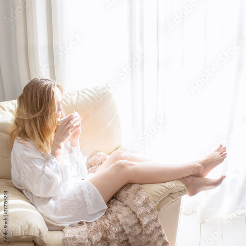 Woman sitting in white armchair and drinking coffee at the morning in bedroom. Relaxing and good morning concept. Fotomurais