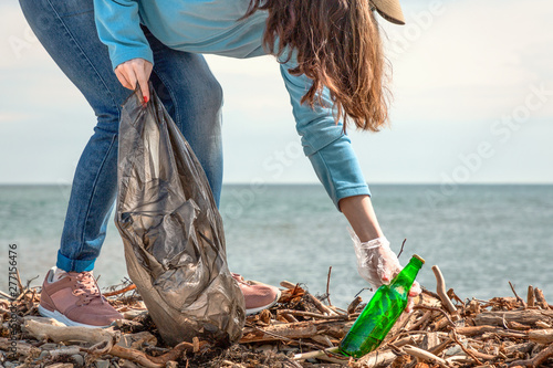 Fotomural A young woman on a clean-up of the coastal area, collecting garbage