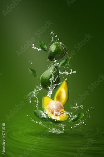Fototapeta Water splashing on Fresh Sliced Green avocado over the Green background. obraz na płótnie