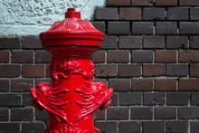 Ornate Old Fire Hydrant Against The Brick Wall