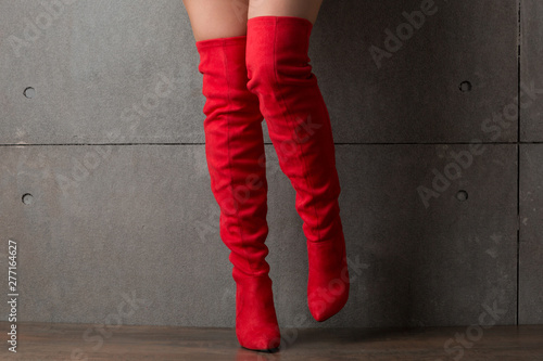 Fototapeta on female sexy legs high red suede boots jackboots, concept, against a concrete wall obraz