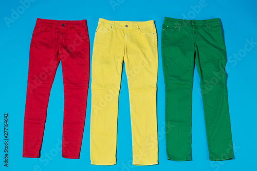 Fotografie, Obraz  three colored pants on a blue background, the concept of a joyful life and shopp