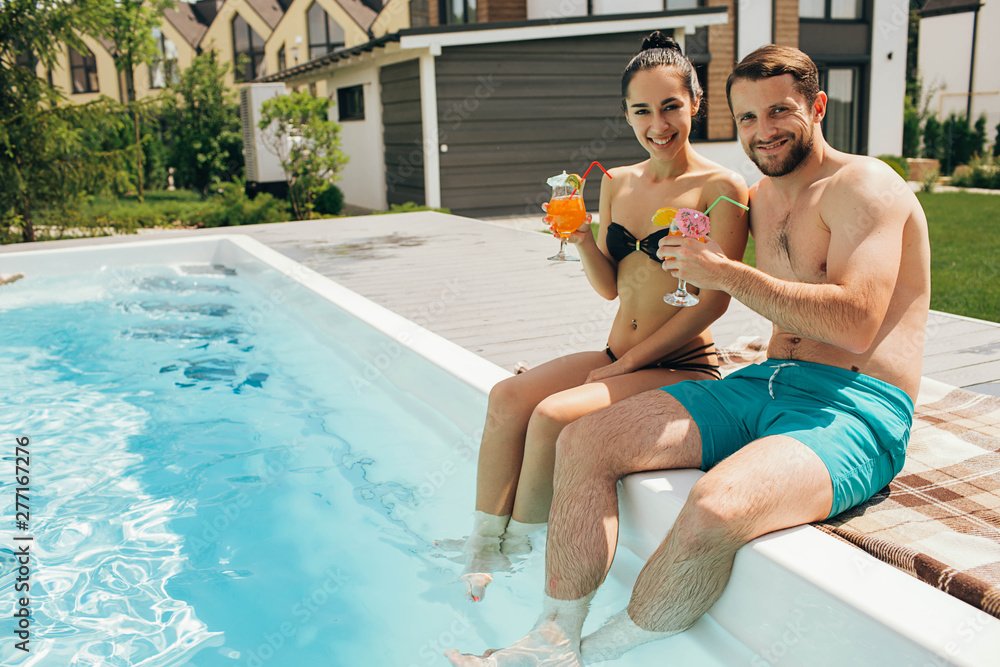 Fototapeta Lovely heteroseksual couple rented a house with a swimming pool. Man and woman sitting near water pool and holding fresh cocktail