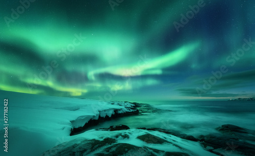 Photo sur Aluminium Aurore polaire Aurora borealis over ocean. Northern lights in Teriberka, Russia. Starry sky with polar lights and clouds. Night winter landscape with aurora, sea with stones in blurred water, snowy mountains. Travel