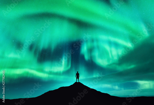 Garden Poster Green coral Aurora borealis and silhouette of a man on the mountain peak. Lofoten islands, Norway. Beautiful aurora and man. Alone traveler. Sky with stars and polar lights. Night landscape with northern lights