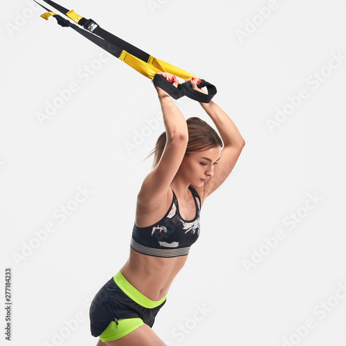 Fotografia Strong woman pulling ropes during suspension training