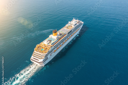 Fotomural Cruise ship liner sails in the blue sea leaving a plume on the surface of the water seascape