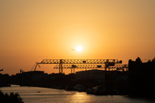 Düsseldorf 2019: Sunset View Of Harbor In Dusseldorf On A Sunny Summer Evening. Image Composition With Rhine, Harbor Crane And Airplane Next To Sun