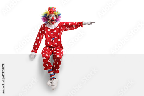 Fototapeta  Clown sitting on a white panel and pointing to the side