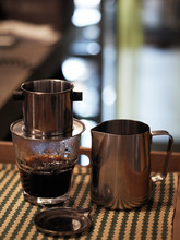 Vietnamese Drip Alternative Coffee Maker Pot Filter On A Glass With A Pitcher From Stainless Steel In Twilight Cozy City Cafe In Warm Vintage Film Tones