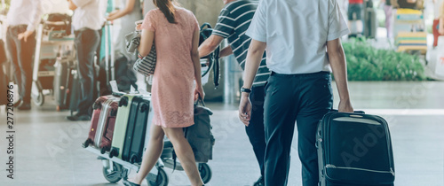 Passengers with big roller luggage stand to wait for the car to pick up at airport arrival terminal Canvas Print