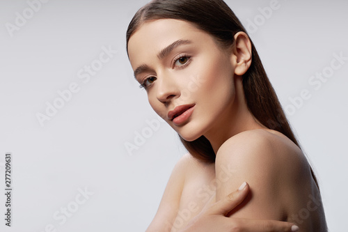 Fotomural Young pretty lady with natural makeup posing against light gray background