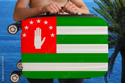Photo tourist holds with two hands a suitcase with the national flag of the Abkhazian