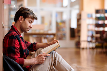Casual young man reading book while sitting by bookshelf