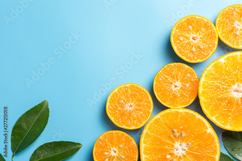 Photo Stands Juice Sliced orange fruits with leaves on blue background, flat design