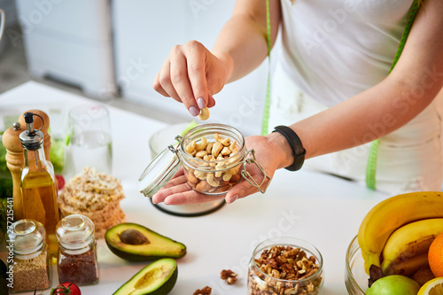 Obraz Young happy woman eating different nuts (cashew, hazelnut, almond) in modern kitchen. Healthy food and Dieting concept. Loosing Weight - fototapety do salonu