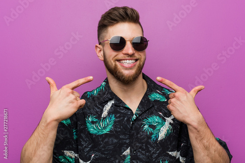 Fotomural Young man wearing a vacation look smiles, pointing fingers at mouth