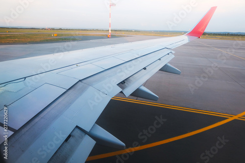 Photo View from the porthole - Wing of an airplane taking off above the runway at high speed during the sunset