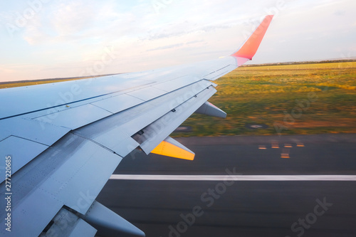Poster Avion à Moteur View from the porthole - Wing of an airplane taking off above the runway at high speed during the sunset. The land is running under the wing