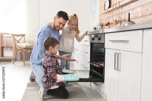 Father with his kids baking cookies in oven at home Wallpaper Mural