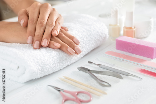 Deurstickers Ontspanning Woman waiting for manicure and tools on table, closeup with space for text. Spa treatment