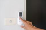 Fototapeta Kawa jest smaczna - Man hand turn on air condition remote switch