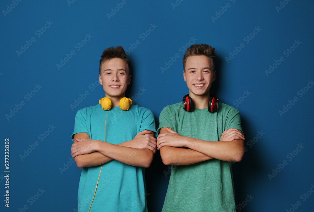 Fototapety, obrazy: Teenage twin brothers with headphones on color background