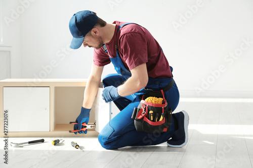 Fotografie, Tablou  Handyman in uniform assembling furniture indoors