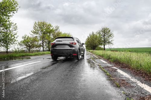 Fotomural  Wet suburban road with car on rainy day