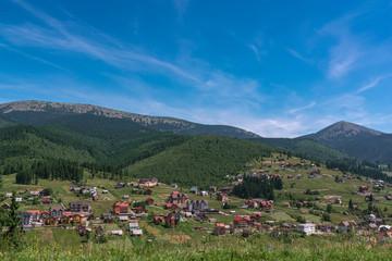 Fototapeta na wymiar Beautiful summer landscape wint mountains. Carpatian village at mountains