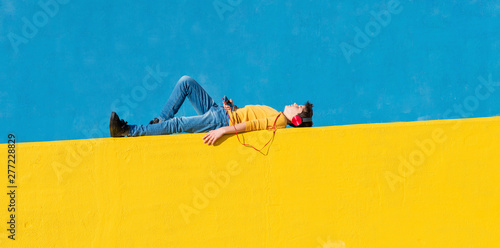 Front view of a young boy wearing casual clothes lying on a yellow fence against a blue wall while using a mobile phone to listening music by headphones - 277228829