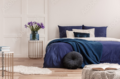 Fényképezés Flowers in vase on bedside table next to king size bed with navy blue bedding