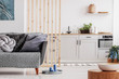 Leinwanddruck Bild - Small studio apartment with contemporary kitchen and grey settee, real photo