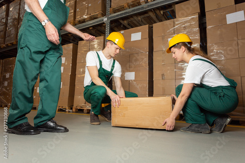 Fotografie, Obraz  Two young warehouse workers in dark green uniforms and yellow helmets lifting he
