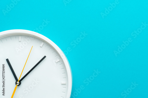 Obraz Part of white wall clock with yellow second hand hanging on wall. Close up image of plastic wall clock over turquiose blue background with copy space. Photo of time management or time is going concept - fototapety do salonu