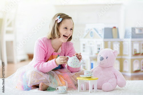 Obraz na plátně Little girl playing with doll house. Kid with toys