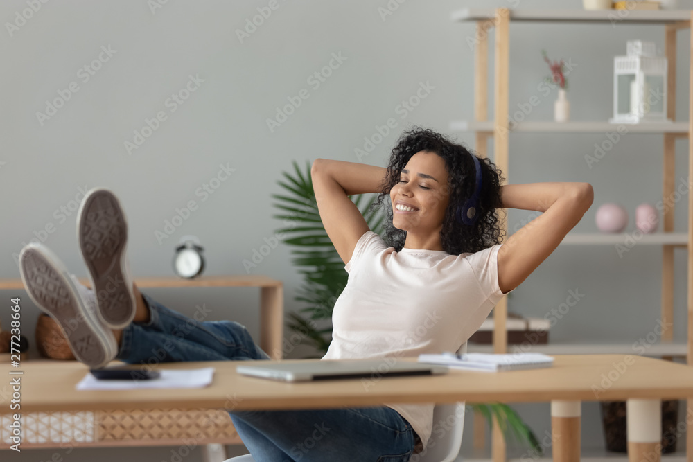 Fototapety, obrazy: Relaxed african woman wear headphones listening to music at desk