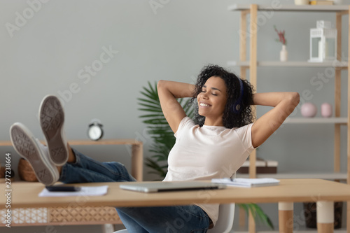 Relaxed african woman wear headphones listening to music at desk - 277238664