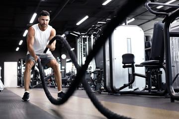 Atletski mladić s bojnim užetom radi vježbu u funkcionalnoj teretani za fitnes.