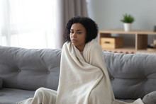 Sick African Woman Feeling Cold Covered With Blanket At Home