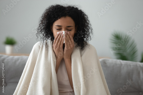 Stampa su Tela  Ill african woman covered with blanket blowing nose got flu