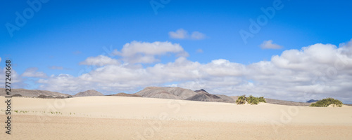Fotografija  Natural landscape with amazing white sand dunes and blue sky with clouds near El Corralejo Fuerteventura Canary Island