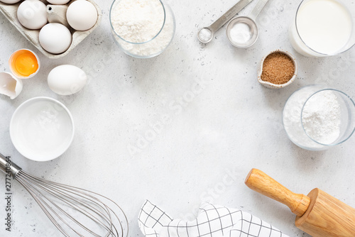 Fototapeta Frame of baking and cooking bread pastry or cake ingredients, flour sugar milk eggs and coconut butter on bright grey background with copy space for text, flat lay obraz