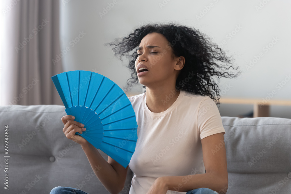 Fototapety, obrazy: Overheated african young woman feeling hot waving fan at home