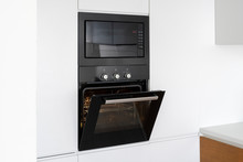 Modern Built In Oven With Open Glass Door On White Kitchen